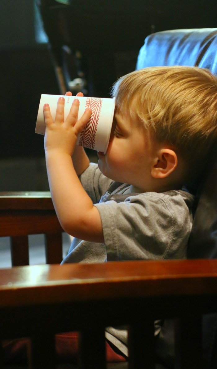 little boy drinking hot chocolate in a comfortable coffee house chair