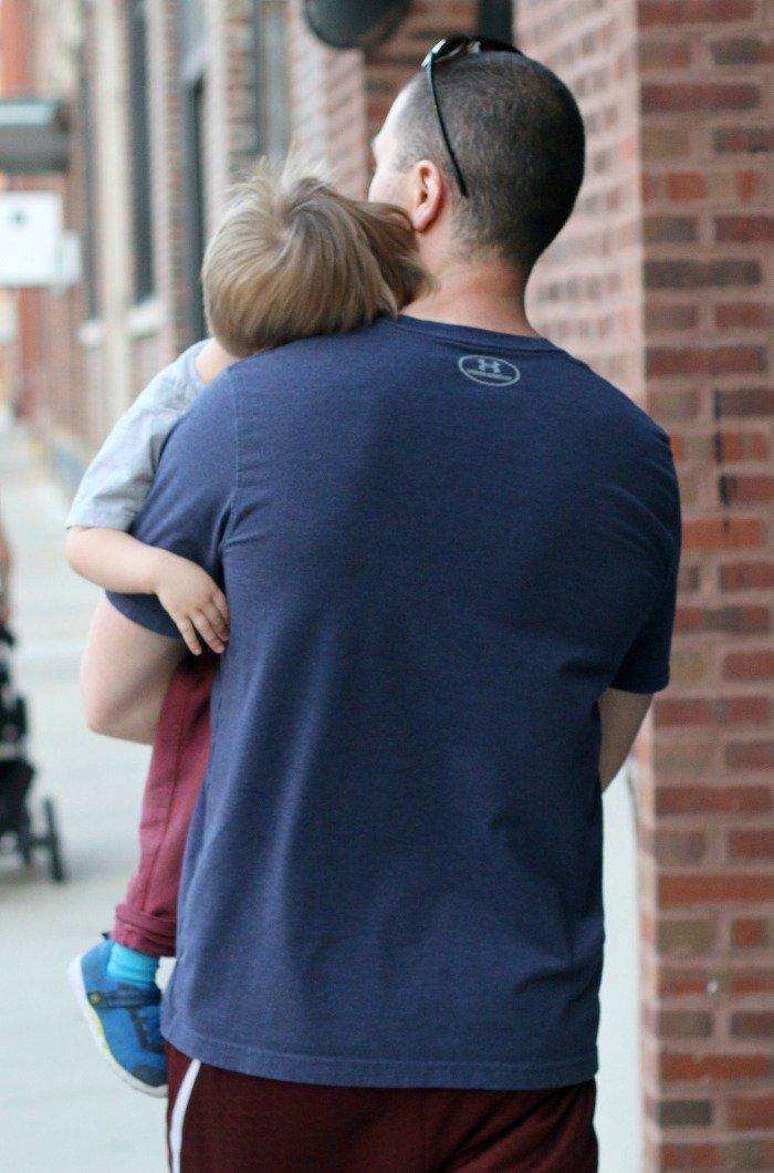 man carrying home a little boy on a sidewalk