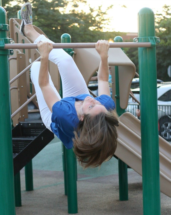 woman playing on the monkey bars at a playground