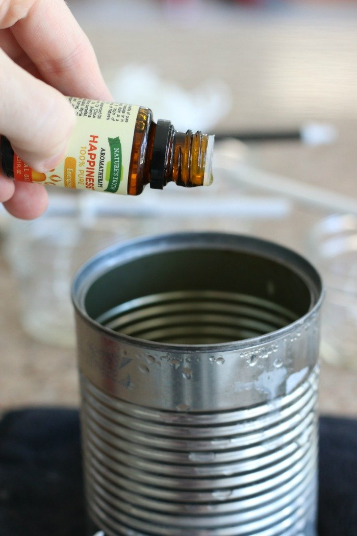 dropping essential oils into melted beeswax