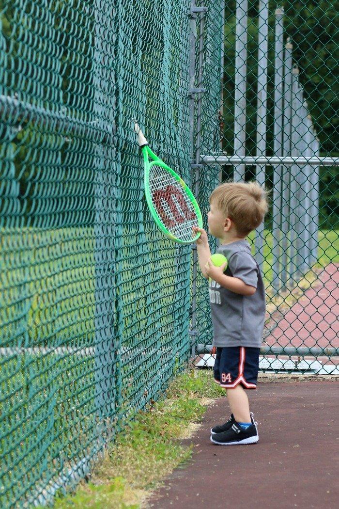 little boy sticking tennis racquet through fence