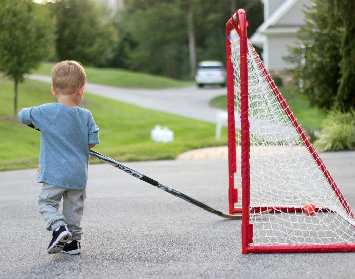 little boy playing hockey i nhis driveway