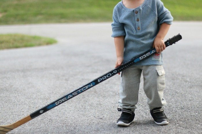 little boy with a large hockey stick playing sports in the driveway