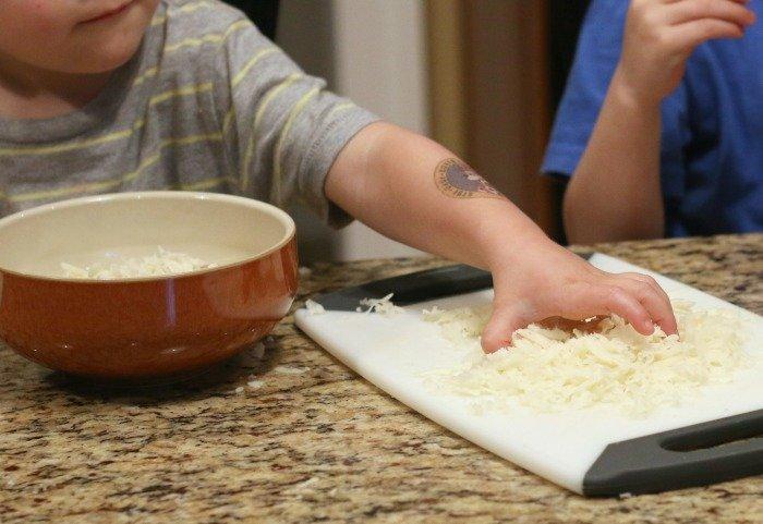 little-boy-reaching-for-shredded-mozzarella-cheese