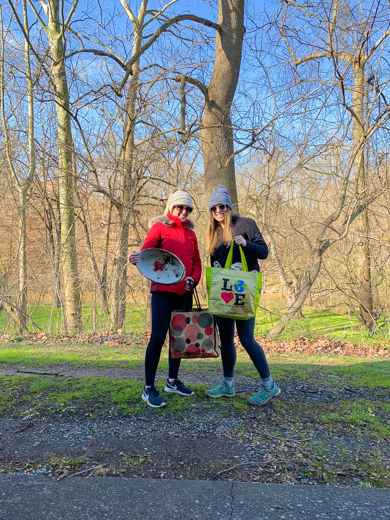 two women holding litter pick up items in the woods