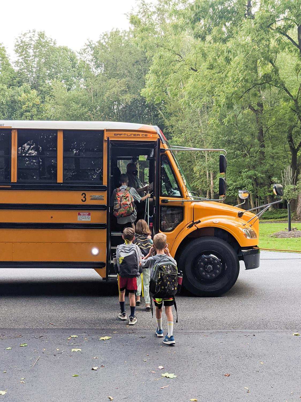 four kids boarding a school bus