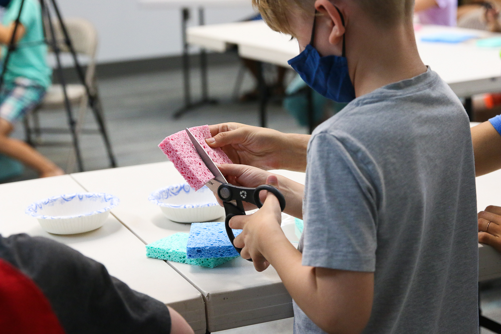 child cutting a sponge to build a sprout house